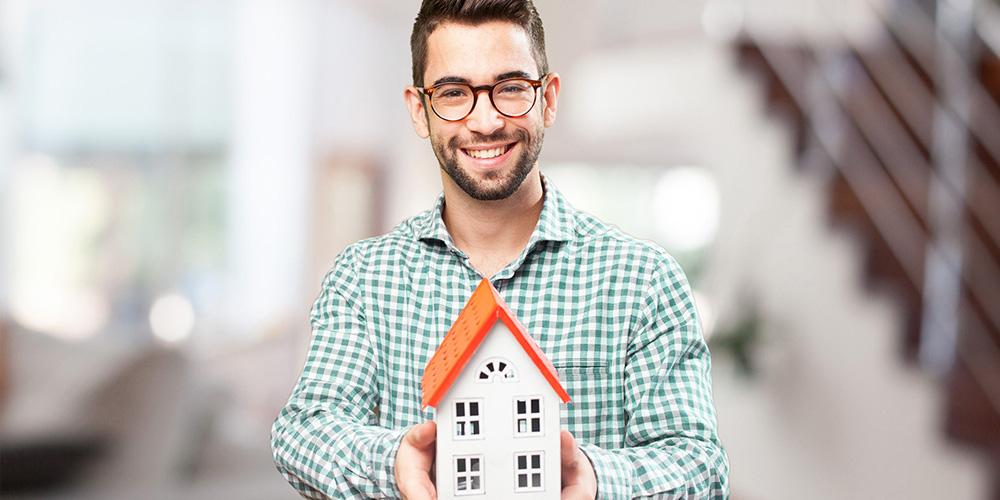 Mand der står med et hus i hånden.